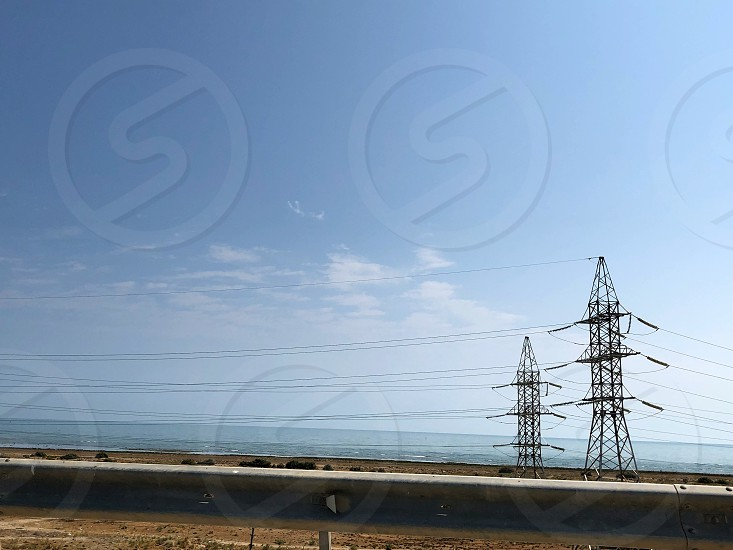 Powerful poles and power lines along the sea. photo