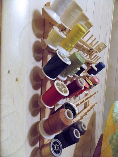 spools of yellow red white blue black and brown threads on wooden wall mounted organizer photo