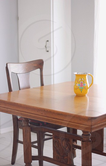 yellow white and pink floral ceramic pitcher on brown wooden dining table photo