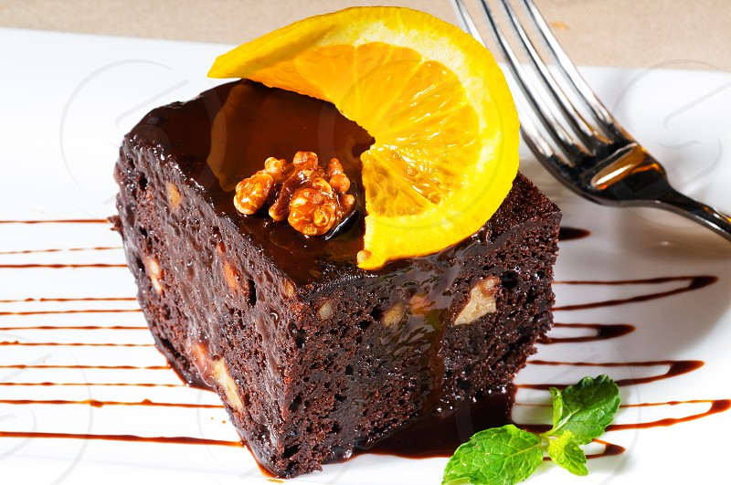 fresh baked delicious chocolate and walnuts cake with slice of orance on top and mint leaf photo