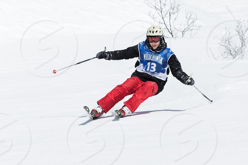 """KAMCHATKA RUSSIA - MARCH 9 2014: Skier rides steep mountains. Competitions freeride skiers and snowboarders """"Kamchatka Freeride Open Cup"""". Russia Far East Kamchatka Peninsula. photo"""
