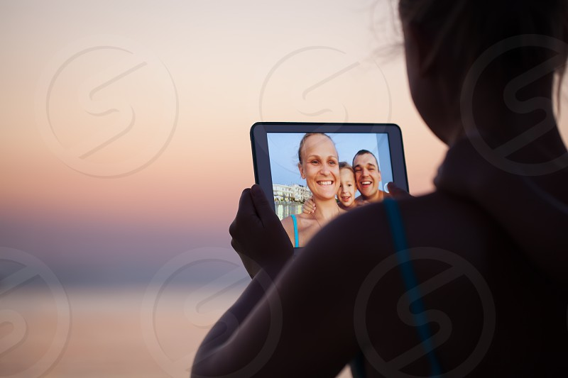 Mother father and son making selfie using tablet computer. They taking picture on resort background photo