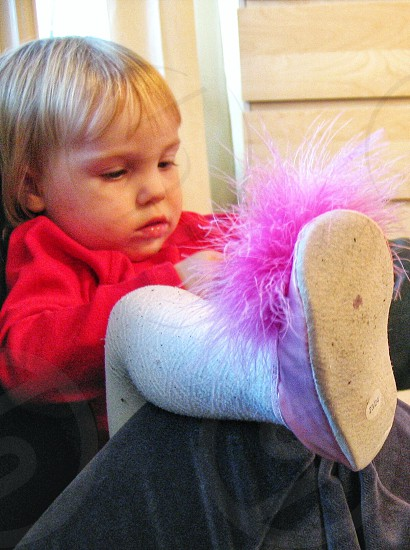 toddler's pink shoe with large pink pom pom photo