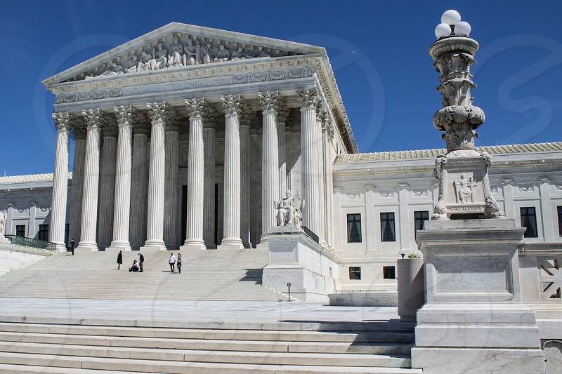 The Supreme Court building in Washington DC with a blue sky background on a sunny day with people in the foreground. photo