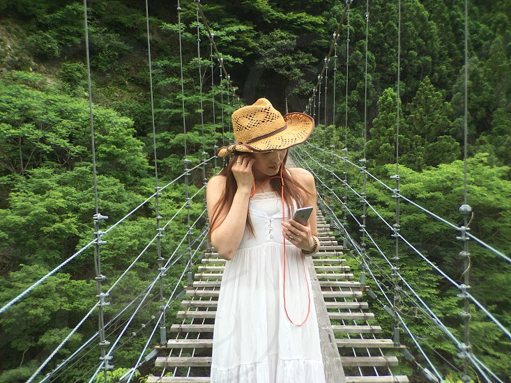 woman in white dress holding smartphone standing on hanging bridge photo