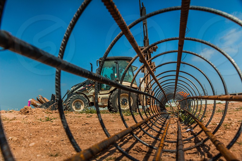 Workers and a tractor with a drilling device at a construction site - view from inside construction steel rod. photo