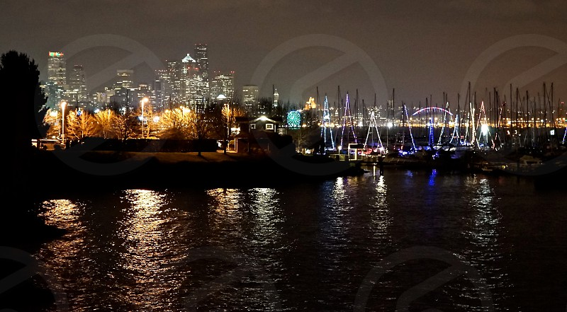 waterfront cityscape night reflections buildings boats masts lighting peaceful contrast seattle photo