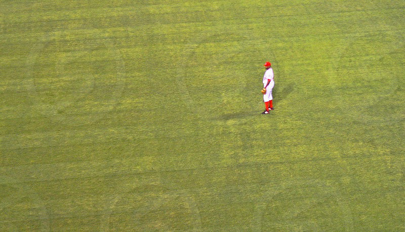 Seen in the distance and from above a baseball outfielder stands in the green grass photo