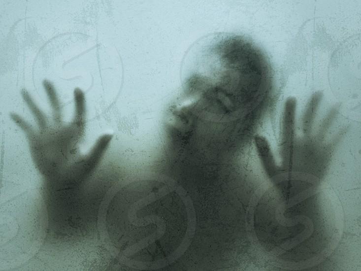 creative portrait dead zombie female against a window glass photo