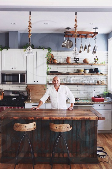 man in white button down shirt standing in kitchen photo