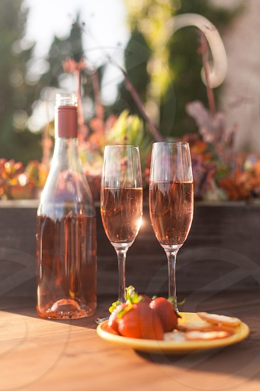 two champagne flutes filled with rose wine on a table next to the bottle and plate of fruit and cheese photo