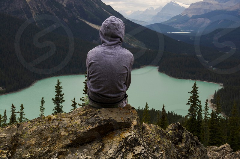 photo of person sitting on cliff facing lake photo