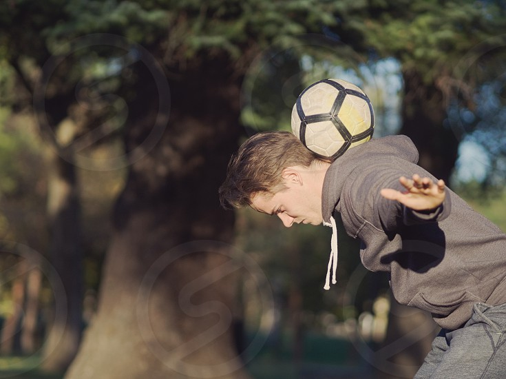 Soccer Player Balancing Football in the Park on a Sunny Autumn Day photo