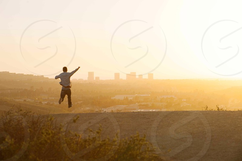 man jumping with sunset view  photo
