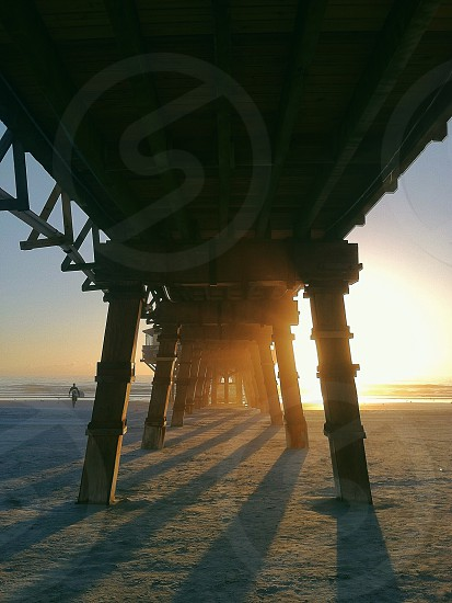 underside view of a brown wooden sea dock during orange sunset photo