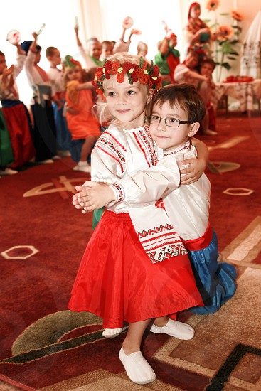 boy and girl dancing on red and brown carpeted room photo