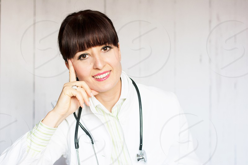 Pretty female doctor wearing white scrubs and stethoscope around her neck photo