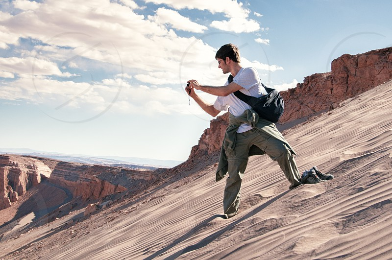 man in a white cotton tee and cargo pants holding a crossbody bag snapping a photo while standing on a sandy hillside with dirt cliffs in the distance photo