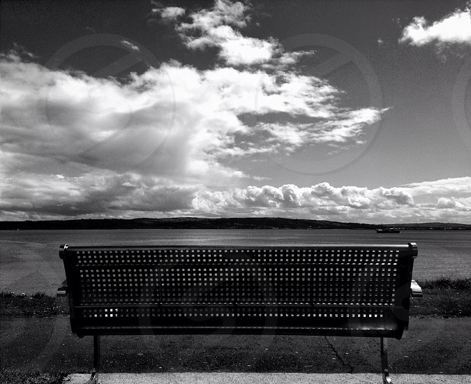 grayscape park bench on sea photography photo