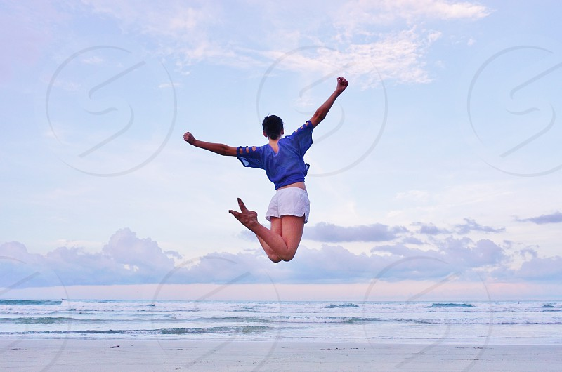 Woman jumping on the beach photo