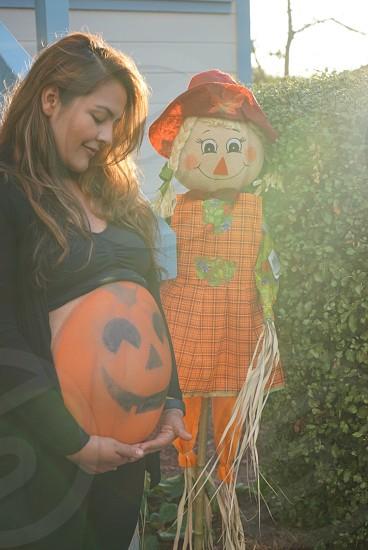 Jack-o'-lantern painted on pregnant woman near scarecrow photo