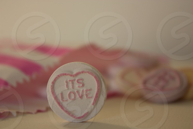 """A love heart sweet saying """"its love"""" with a bag of sweets in the background photo"""