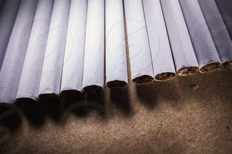 Abstract composition of bunch of cigarettes on brown surface.  photo