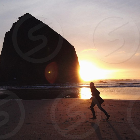 woman running near the seashore with rock formation photo