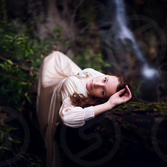 woman wearing white dress lying on tree trunk photo