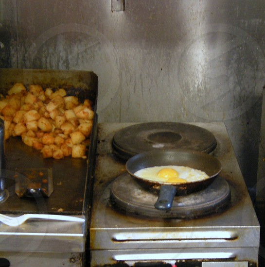 Egg frying in pan next to potatoes on griddle photo