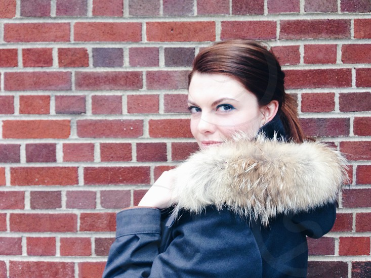 woman in black parka coat smiling and standing beside red brick wall photo