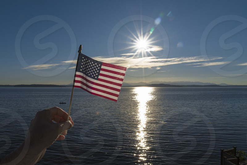 Point of view waving a small American flag with sunburst over the sea. photo