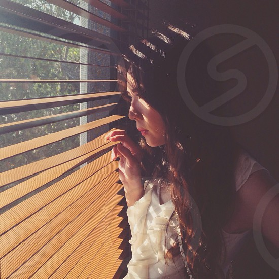 woman looking out window blinds photo