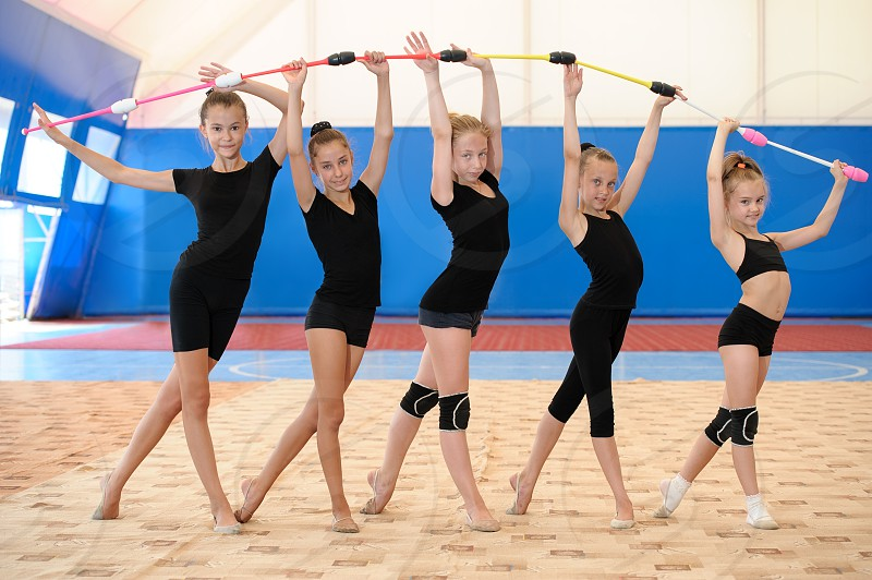 Five young female gymnasts standing by age and making bow with Indian clubs photo