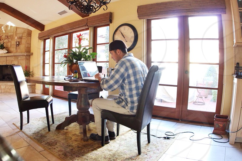 person wearing gray and white checkered long sleeve polo using laptop computer on dining table photo