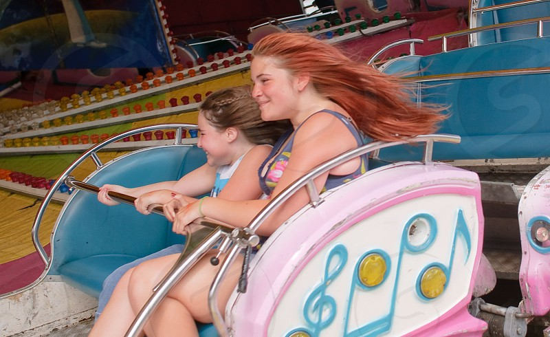 woman and girl riding amusement ride during day photo