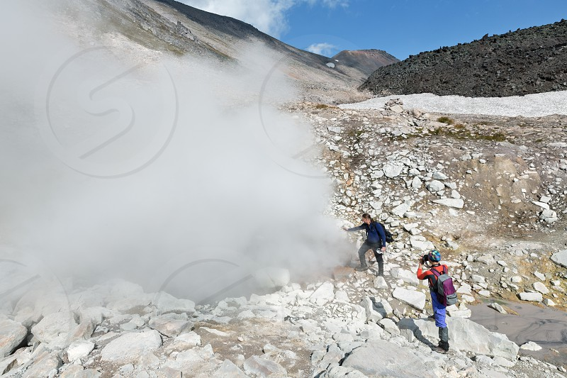 NALYCHEVO NATURE PARK DZENZUR VOLCANO KAMCHATKA PENINSULA RUSSIAN FAR EAST - SEP 4 2014: Young man and woman - tourists standing by smoking fumaroles on crater active Dzenzur Volcano on sunny day. photo