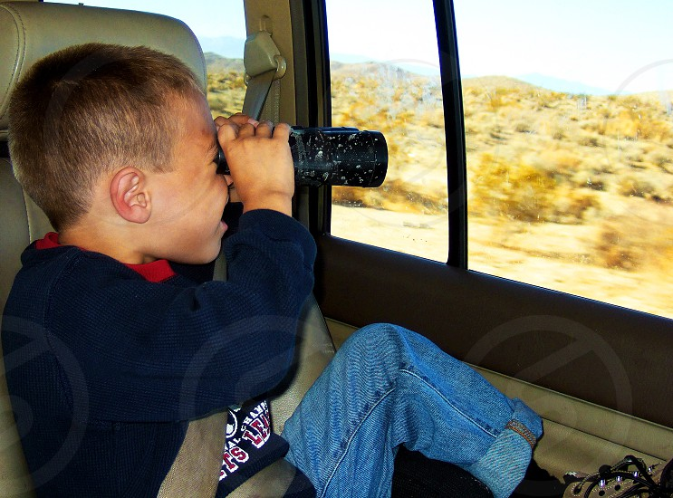 Little boy in the back seat of a car uses binoculars to look out at the desert. photo