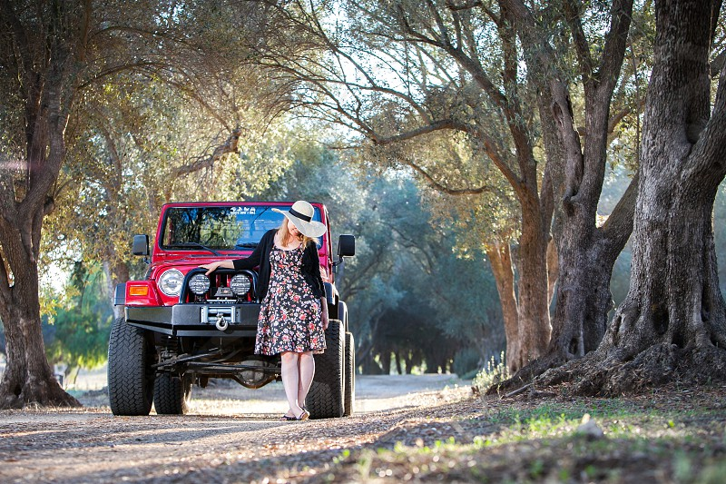 A girl and her jeep under a canopy of trees.  Leaves branches dirt mountain dirt off road red explore sun flare winch tires lights. Woman hat dress sweater. (All logos changed or removed) photo