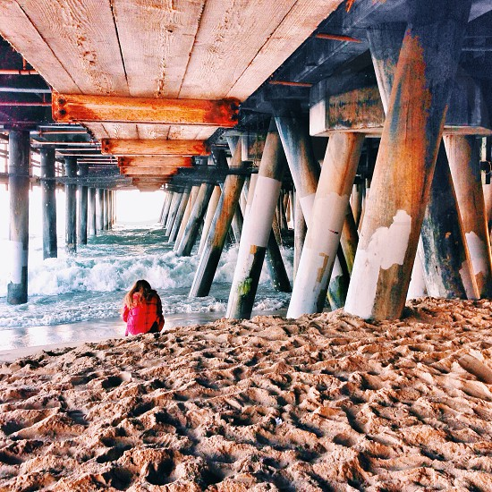 woman in red coat sitting under a pier photo