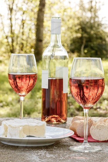 two glasses of rosé wine next to the bottle a plate with cheese some bread on table outdoor. Trees can be seen in the background but out of focus. photo