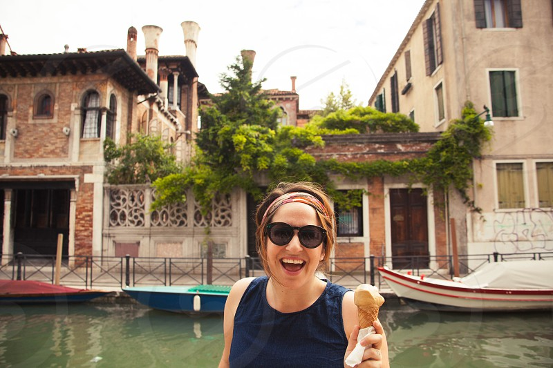 A happy girl eats gelato in Italy photo