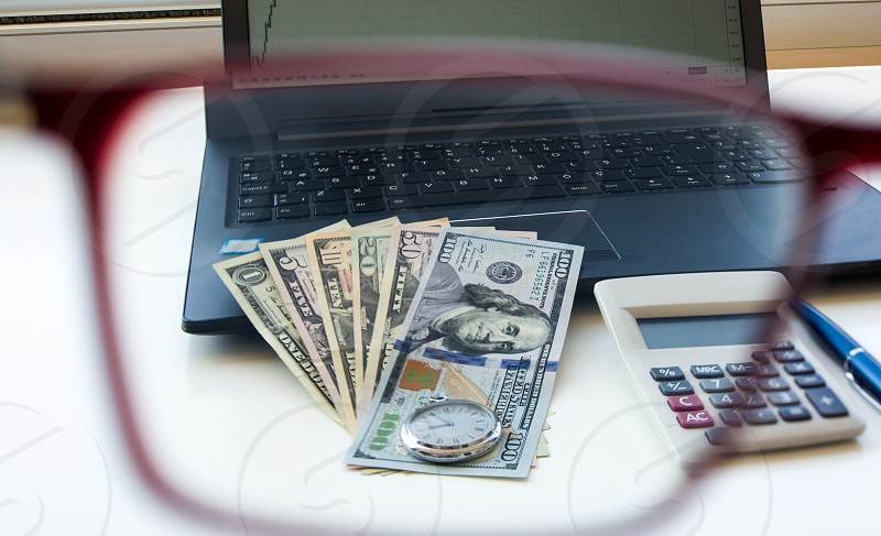 Us Dollars laptop and calculator on white background photo