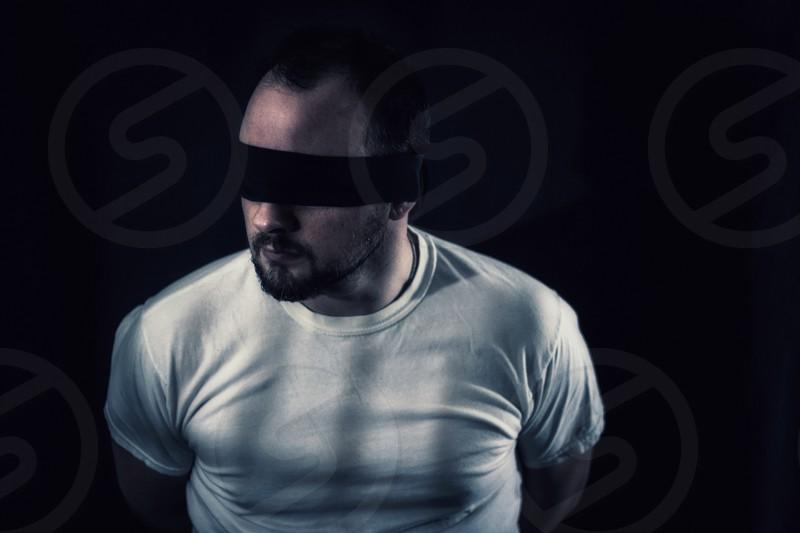 man wearing  white crew neck t-shirt  on a blind fold photo
