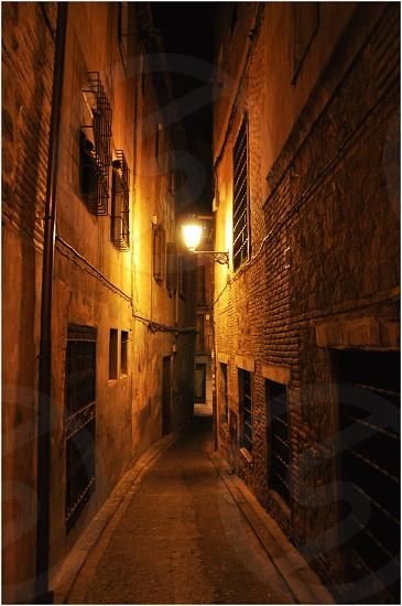 brown bricked walls in between pathway photo