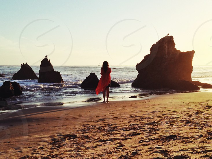 woman in pink dress standing near sea shore photo