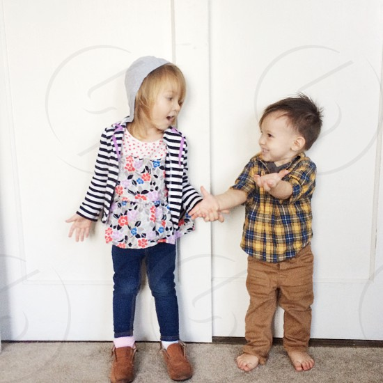 2 kids leaning on wall photo