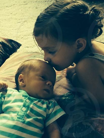 girl kissing baby photo