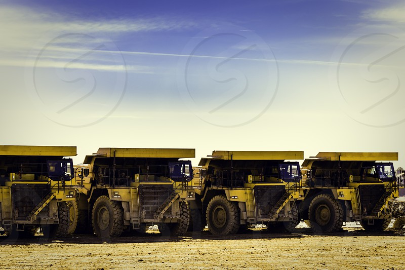 Four yellow dumper trucks in mine put in row with blue sky background and clouds photo