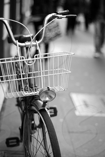 wire basket on commuter's bicycle in grayscale photo
